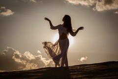 在日落的美好的妇女跳舞 免版税库存图片