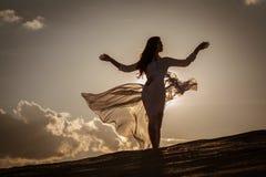 在日落的美好的妇女跳舞 免版税库存照片