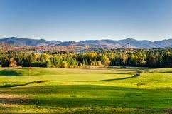 在日落的美好的山风景与前景的一个高尔夫球场 库存图片