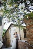 在日落的美好的新娘夫妇在威尼斯街道上 图库摄影