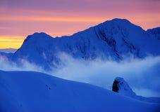 在日落的美好的高山风景与云彩和海覆盖 Fagaras山在冬天 免版税库存照片