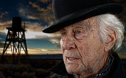 在日落的老人和水塔 免版税库存照片