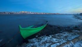在日落的老小船在多瑙河在冬天 图库摄影