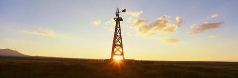 在日落的老木风车 免版税库存照片