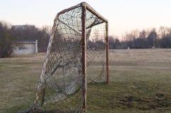 在日落的老生锈的足球目标 免版税图库摄影