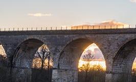 在日落的老铁路高架桥 图库摄影