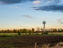 在日落的老水风车 库存照片