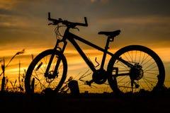 在日落的自行车剪影 免版税库存图片