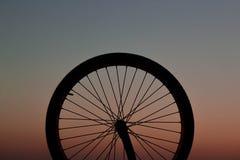 在日落的自行车车轮 免版税图库摄影