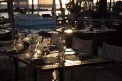 在日落的花梢室外餐馆桌设置 免版税库存照片