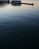 在日落的蓝色和橙色水与船坞 免版税库存图片