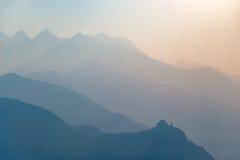 在日落的蓝色被定调子的山剪影和修道院外形 免版税库存照片