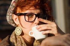 在日落的行家女孩饮用的coffe 免版税库存图片