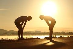 在日落的被用尽的和疲倦的健身夫妇剪影 库存照片