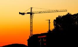 在日落的起重机与橙色和黄色 库存图片