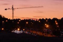 在日落的起重机塔在有被点燃的灯笼的一个城市 免版税库存照片