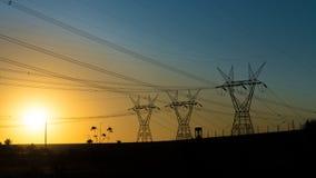 在日落的输电线在伊泰普水电站水坝附近 免版税库存图片