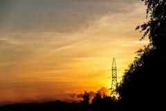 在日落的输电线 免版税库存图片
