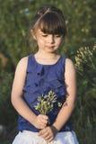 在日落的逗人喜爱的小女孩posig与花 免版税库存照片