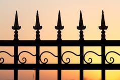 在日落的金属篱芭 免版税库存照片
