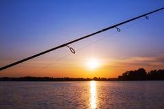 在日落的钓鱼竿 免版税库存照片