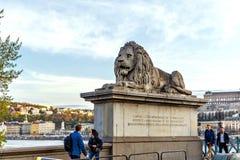 在日落的铁锁式桥梁狮子与游人 免版税库存图片