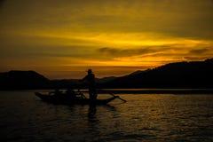 在日落的长平底船小船 免版税库存照片