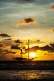 在日落的颜色的剧烈的海和运输小船 图库摄影