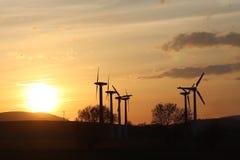 在日落的风力驻地 浪漫晚上和生态上干净的电现代技术  enviro的保护 免版税库存图片