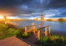 在日落的风车在小孩堤防,荷兰 土气横向 图库摄影
