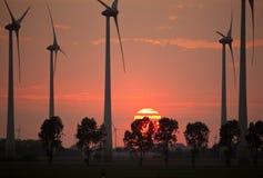 在日落的风轮机在工作 库存照片