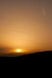 在日落的飞机足迹 免版税库存图片