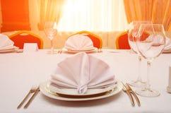 在日落的餐馆制表晚餐或宴会的设置 免版税库存图片