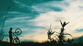 在日落的骑自行车者上升的山 免版税库存照片