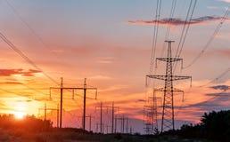 在日落的高压输电线 电发行驻地 高压电传输塔 免版税库存图片