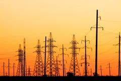 在日落的高压输电线 免版税库存照片