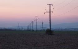 在日落的高压输电线 免版税库存图片