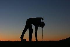 在日落的高尔夫球运动员剪影 免版税库存图片