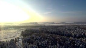 在日落的鸟瞰图在降雪 高速公路通过冬天森林和领域 背景的冻在雪的河和小山 股票视频