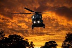 在日落的直升机 库存图片