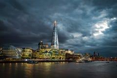 在日落的黑暗的云彩周围伦敦的地平线 免版税库存照片