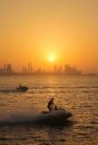 在日落的巴林地平线与速度小船 库存图片