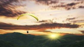 在日落的滑翔伞与紫色云彩 库存图片