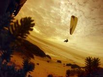 在日落的滑翔伞飞行 库存照片