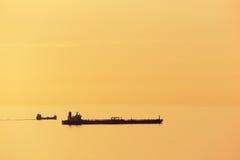 在日落的货船与风平浪静 免版税库存照片