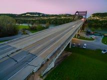 在日落的紫色和桃红色有角度的空中Pennybacker桥梁与显示从长的曝光的汽车行动采取由寄生虫 免版税库存图片
