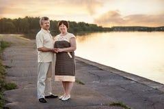 在日落的年长夫妇在湖河附近 免版税库存图片