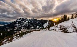 在日落的滑雪坡道与剧烈的云彩 库存图片