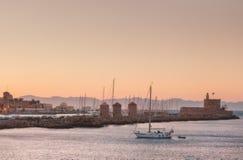 在日落的Mandraki口岸从风车和城堡 罗得岛海岛  希腊 库存照片