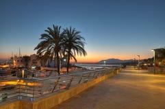 在日落的Marbella港口和峭壁 免版税图库摄影